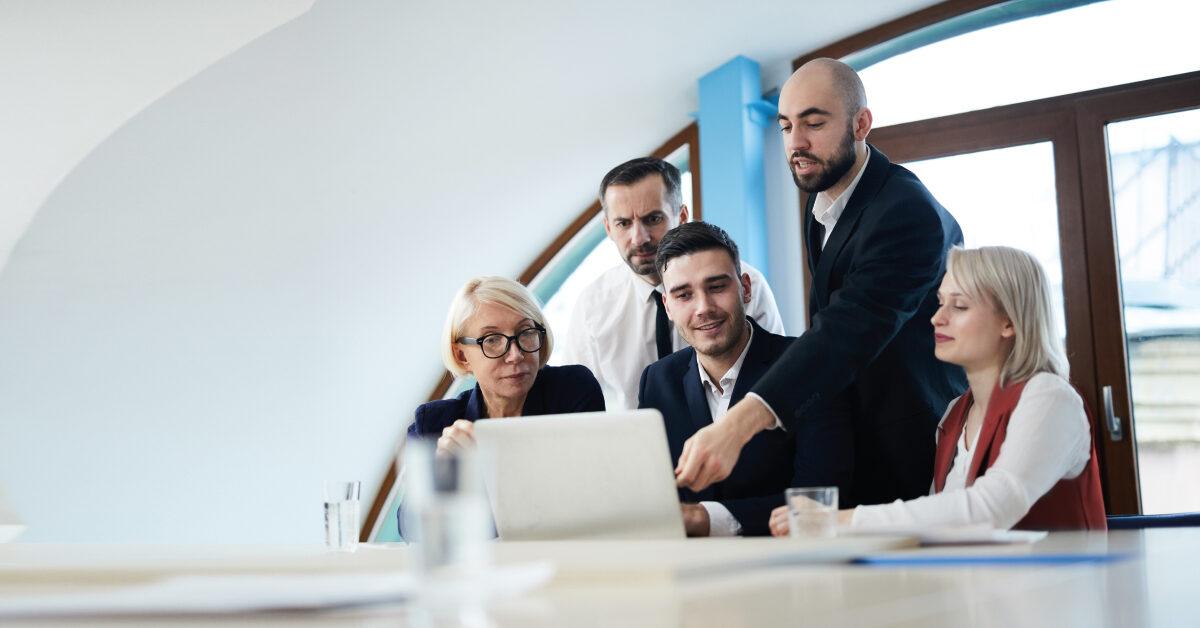 Personas que miran una pantalla de computadora en un entorno corporativo